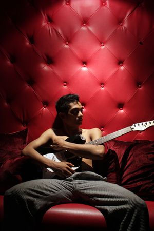 Ziggy, shirtless, hugging a guitar while sitting on a bright red background